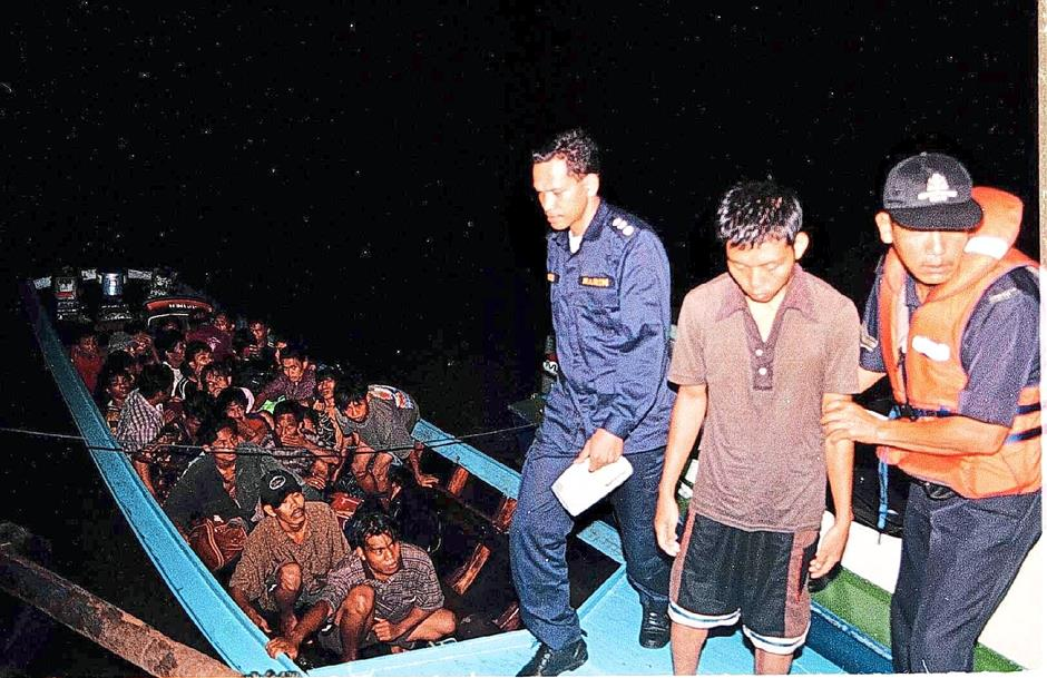 Marine policemen taking away a boat full of illegal immigrant who were caught off Pulau Besar for illegal entry into the country .