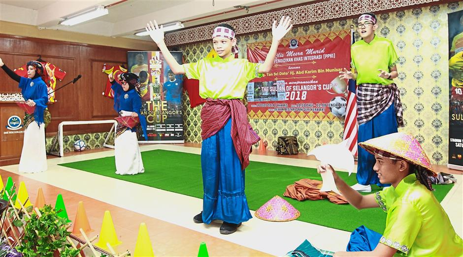 Students from SMK Seri Keramat's Special Needs Integration Programme (PPKI) performing a cultural dance for the organising committee during the ticket handover ceremony.
