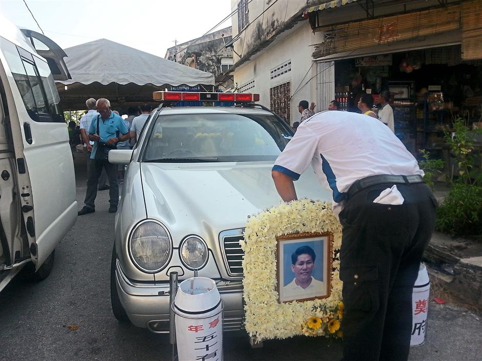 Getting ready: A worker attaching the late Chang's photo on the hearse before the funeral procession.