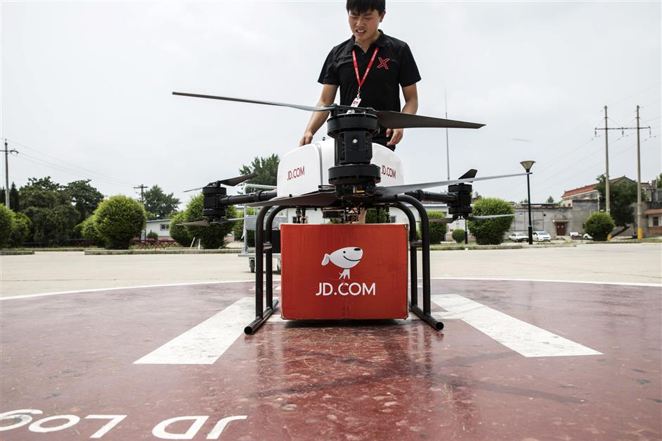 An employee prepares a JD.com Inc. drone during a package delivery demonstration at a launch pad of the company\'s drone testing site in Xi\'an, China, on Tuesday, June 19, 2018. JD.com is racing companies from across the world to develop unmanned aerial vehicles with the strength, range and reliability to deliver goods on a large scale and solve the expensive u201clast-mileu201d problem for couriers. Photographer: Qilai Shen/Bloomberg