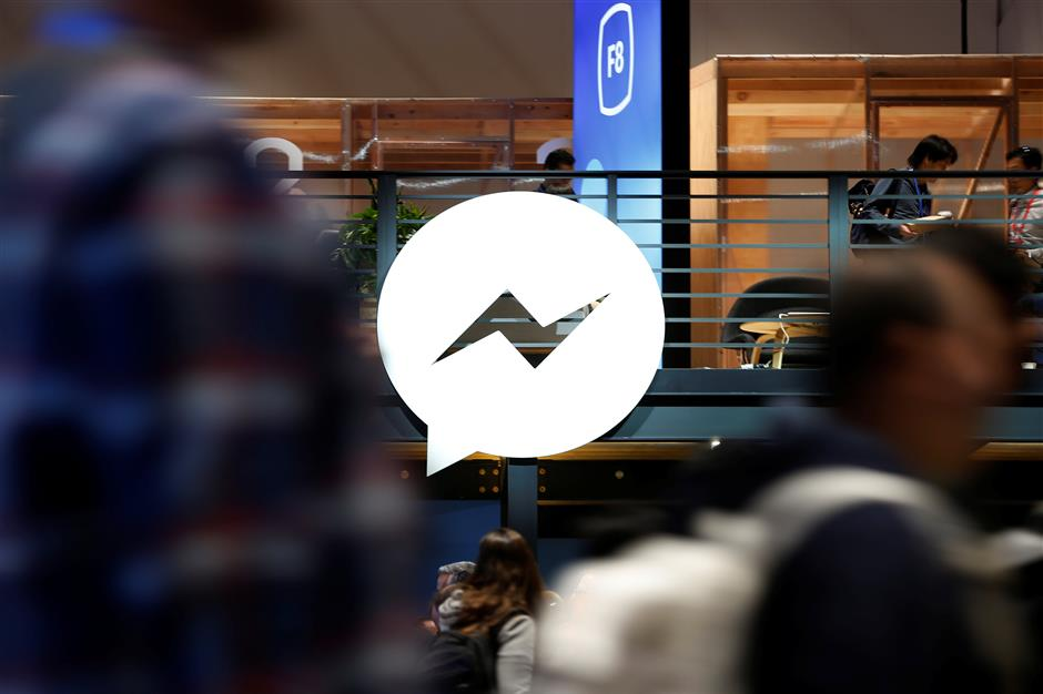 Attendees walk past a Facebook Messenger logo during Facebook Inc\'s annual F8 developers conference in San Jose, California, U.S. May 1, 2018. REUTERS/Stephen Lam