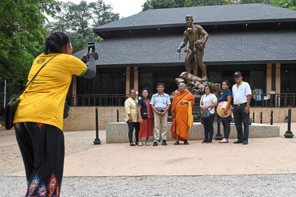 One for the album: Visitors posing for photos in front of a statue of Thai diver Saman Gunan at the visitor centre near the Tham Luang cave entrance. u2014 AFP