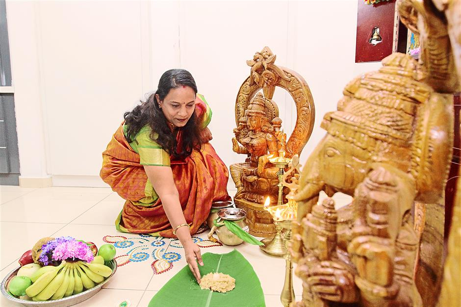 An offering to God: Geetha placing some sweet ponggal on a banana leaf.