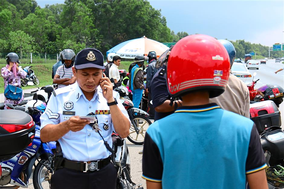 No escape: A traffic policeman checking a motorcyclist's licence for any summonses during an 'Ops Warta' roadblock.