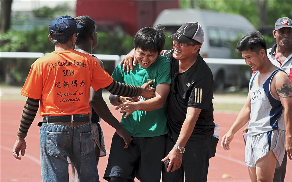 Wong (in cap) congratulating one of his students after winning an event. 11th Exodus Games 2018 at Panasonic Sports Complex, Shah Alam