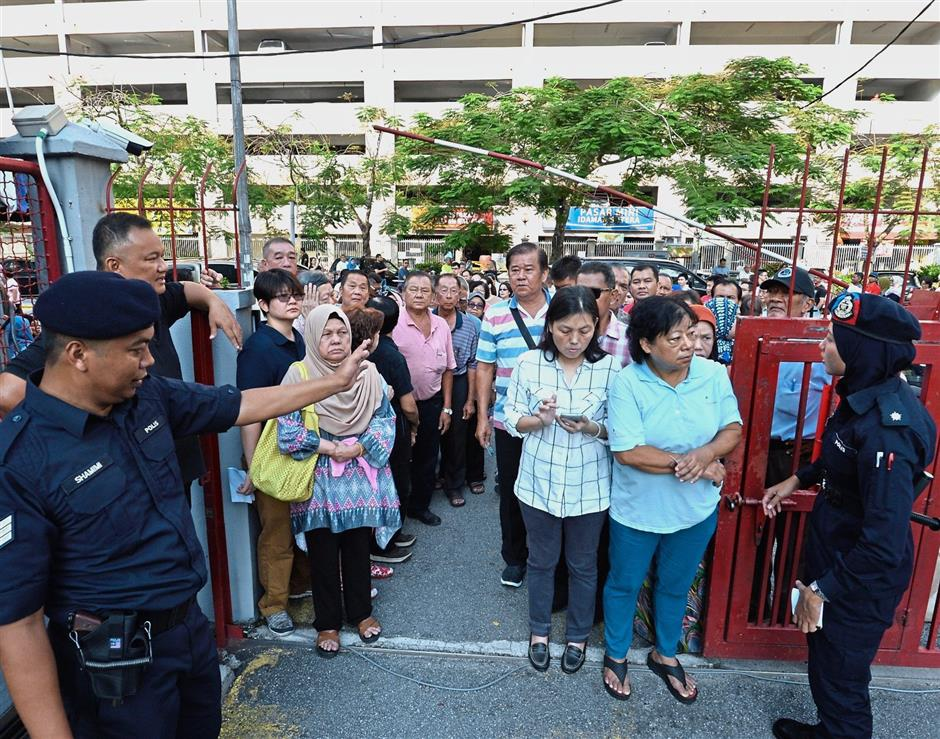 Voters were already gathered at the gate outside SJK(C) Lee Rubber in Wangsa Maju before the start of voting at 8am. — Ong Soon Hin/The Star