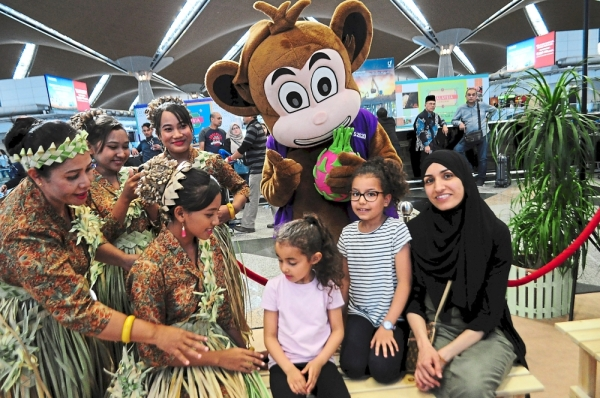 French tourists taking a photograph with Mah Meri dancers from Bukit Bangkung and the Visit Sepang Year 2020 mascot.