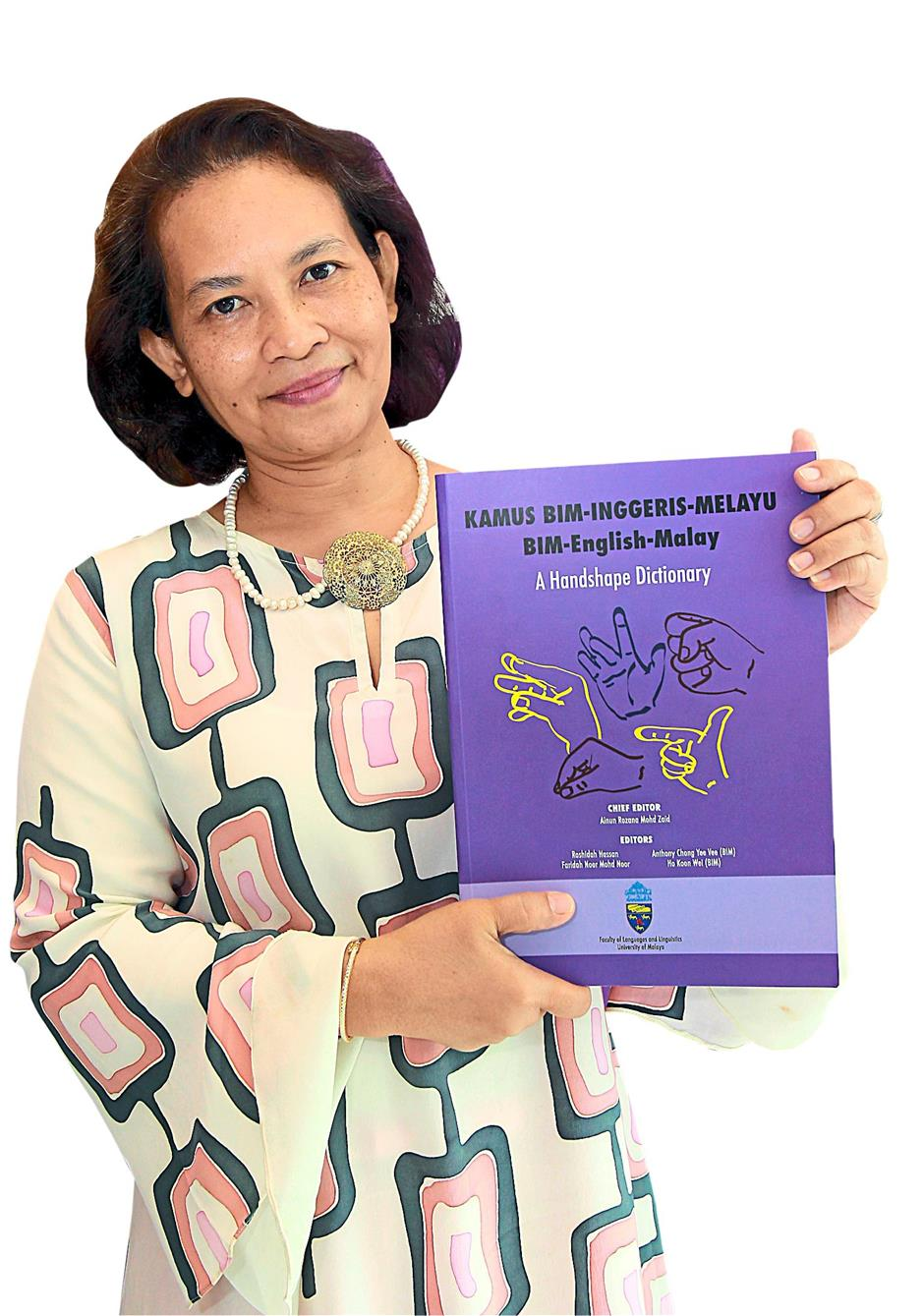 Universiti Malaya's Faculty of Language and Linguistics senior lecturer Ainun Rozana Ainun Mohd Zaid holds up a copy of the BIM-Malay-English Hanshape Dictionary, during its launch at the university in Kuala Lumpur. -Art Chen / The Star. 17 July 2014.
