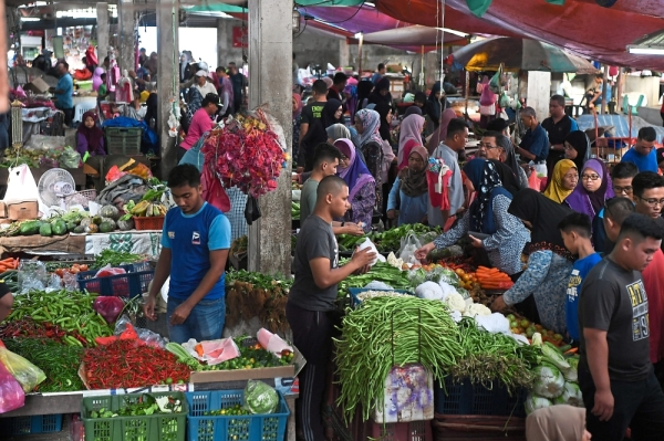 Preparing for a feastMuslims shopping for ingredients at a market in Kuala Terengganu as                  preparations for Hari Raya Aidilfitri kicks into gear. Chicken, ikan tongkol and vegetables are among the necessities for traditional fare like nasi dagang,           nasi minyak and rendang that is a must for open house. — Bernama