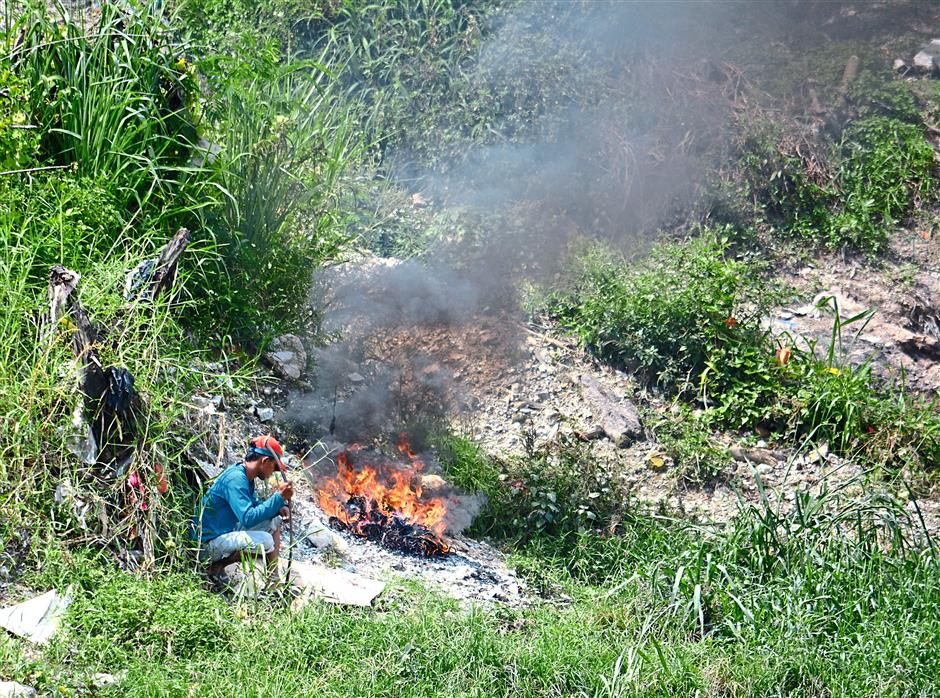 Air pollution: A man burning some of the collected waste along Sungai Kelang. The burning of the waste is done to separate recyclables. However, this could lead to peat fires.