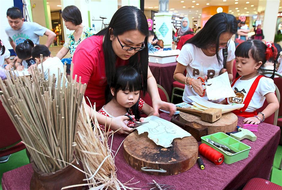 Loke Wai Peng, 35, helping her daughter Janice Chin, five, to cut out the puppet drawing in a workshop at Queensbay Mall.Starpic by: CHIN CHENG YEANG/The Star/01-08-2015