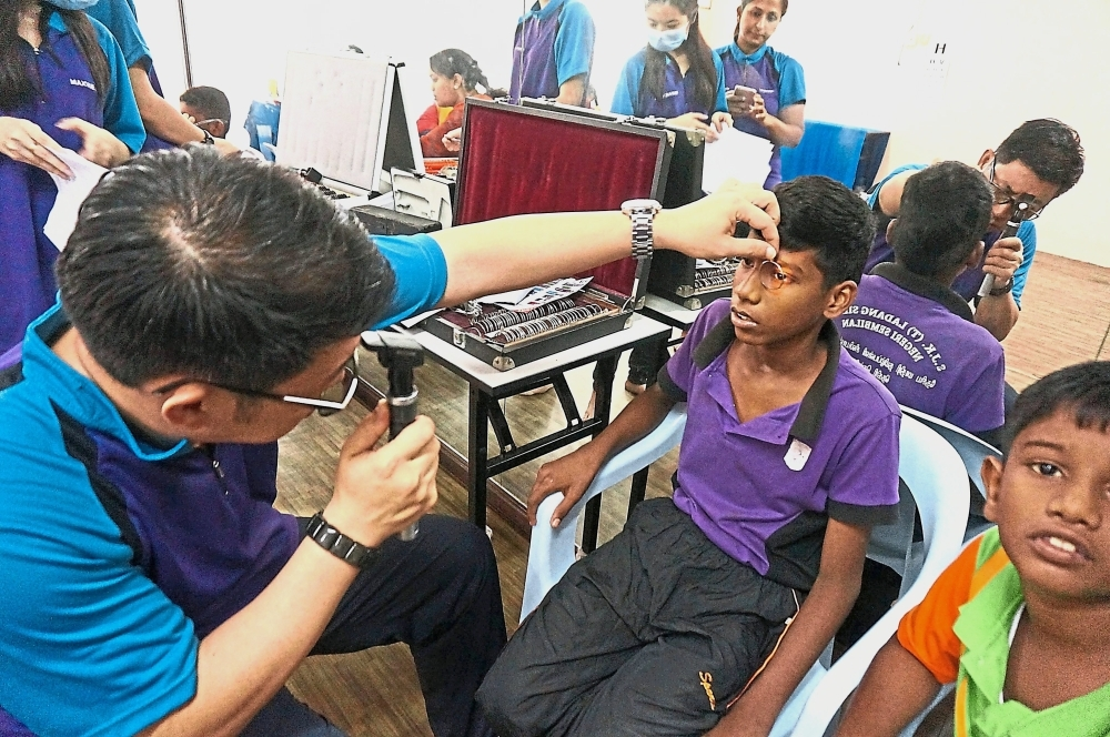 Maxvue Vision has worked with schools to provide free eyewear for underprivileged students. Featured here is a volunteer optometrist carrying out eye checks at SJK(T) Ladang Sialang in Bahau, Negri Sembilan.