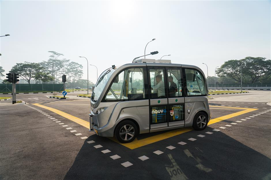 Passengers ride in a Navya SAS autonomous electric passenger bus travelling along the test circuit at the Centre of Excellence for Testing & Research of Autonomous Vehicles (CETRAN) of Nanyang Technology University in Singapore, on Tuesday, May 22, 2018. In the race to deploy driverless public transport, Singapore has built a mini town that could vault it into pole position. The 2-hectare complex, unveiled in November, has intersections, traffic lights, bus stops and pedestrian crossings, all built to the specifications that Singapore uses for its public roads. Photographer: Nicky Loh/Bloomberg