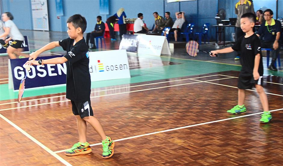 Ong Ting Yong (right) keeps a close watch as his partner Ooi Ee Wei executes a service during the Boys Under-10 doubles.
