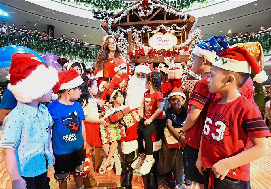 Children mingling with Lawrance Ayerru in Santa Claus attire and Saskia Von Wehdran as Santarina (behind) at Queensbay Mall's Christmas Fairy Land. (Right) Pedestrians passing by the snowman and snowflakes festive display in front of Gama Supermarket and Departmental Store.