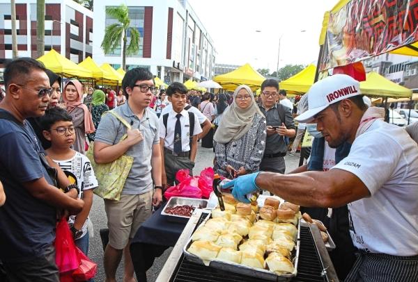 Classic choice: Burger Hardcore owner Arhaban Ismail (right) preparing burgers for customers  at the TTDI bazaar in Kuala Lumpur.