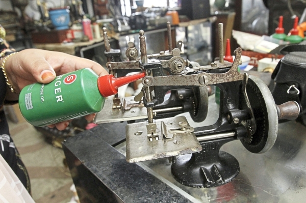 An antique mini sewing machine unit being oiled.