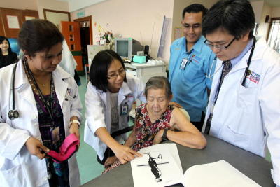 In good hands: Dr Tan Maw Pin explaining the different physiotherapy exercises to Bong Fah Heong, surrounded by (from left) Dr Shahrul Bahyah Kamaruzzaman, Lokman Abdul Majid and Dr Chin Ai-Vyrn, at Universiti Malaya Medical Centre.