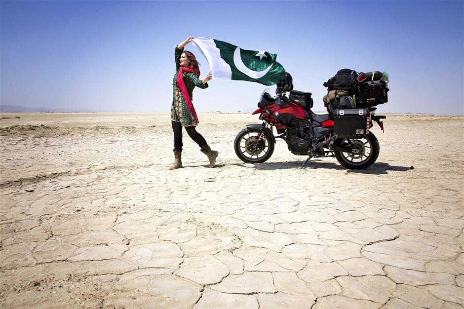 """CORRECTION - This handout picture taken on March 20, 2019, and released by Canadian tourist Rosie Gabrielle shows Gabrielle posing for photographs as she holds a Pakistani flag during her motorcycle trip in southwestern Balochistan province in Pakistan. - They are young, Western, and full of praise for Pakistan: Travel influencers have discovered the land of the pure but critics warn their rose-tinted filters are selling an inaccurate picture of the conservative, militancy-scarred country. (Photo by HANDOUT / Rosie Gabrielle / AFP) / TO GO WITH: Pakistan-travel-socialmedia-influencers-security, FEATURE by Joris Fioriti -----EDITORS NOTE --- RESTRICTED TO EDITORIAL USE - MANDATORY CREDIT 'AFP PHOTO / Rosie Gabrielle ' - NO MARKETING - NO ADVERTISING CAMPAIGNS - DISTRIBUTED AS A SERVICE TO CLIENTS - NO ARCHIVES / """"The erroneous mention[s] appearing in the metadata of this photo by HANDOUT has been modified in AFP systems in the following manner: [ADDS HANDOUT RESTRICTIONS]. Please immediately remove the erroneous mention[s] from all your online services and delete it (them) from your servers. If you have been authorized by AFP to distribute it (them) to third parties, please ensure that the same actions are carried out by them. Failure to promptly comply with these instructions will entail liability on your part for any continued or post notification usage. Therefore we thank you very much for all your attention and prompt action. We are sorry for the inconvenience this notification may cause and remain at your disposal for any further information you may require."""""""