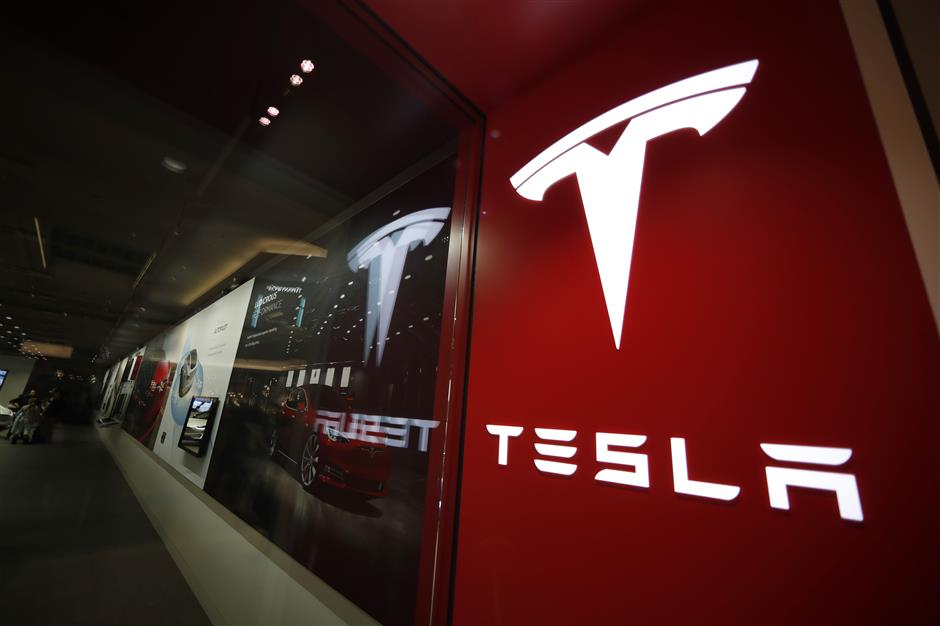 FILE- In this Feb. 9, 2019, file photo, a sign bearing the company logo is displayed outside a Tesla store in Cherry Creek Mall in Denver. Tesla is walking back its plan to close most retail stores worldwide. The company says it still plans to move to fully online sales but it wonu2019t close as many stores as originally thought. Tesla announced last month that it would shutter most of its stores to cut costs so it could make money on the $35,000 Model 3 electric car. Tesla now says it closed 10 percent of its stores, but a few of those will be reopened.   (AP Photo/David Zalubowski, File)