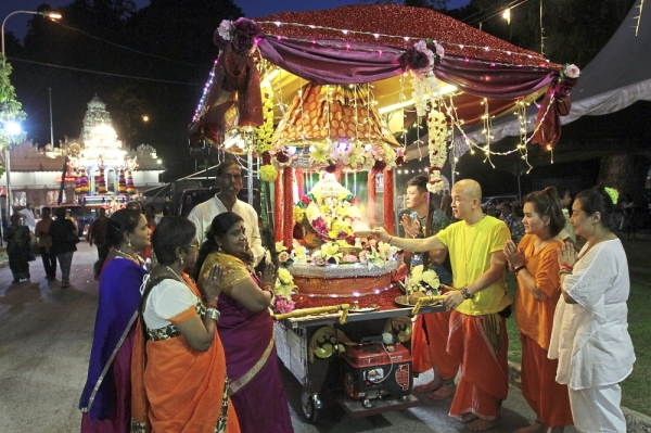 Lim (in yellow) and Wong (second right, in orange) joining other devotees in offering prayers to Lord Ganesha at the Bhajan cart as the chariot prepares to leave the Arulmigu Balathandayuthapani Hilltop Temple in Waterfall Road. (Left pic, from left) Luoto and Rautavaara from Finland enjoying the Chitraparuvam Festival.