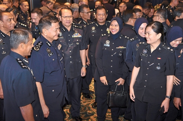 All smiles: Abdul Hamid (second from left) mingling with other police officers during the annual general meetings in Melaka.  u2014 Bernama