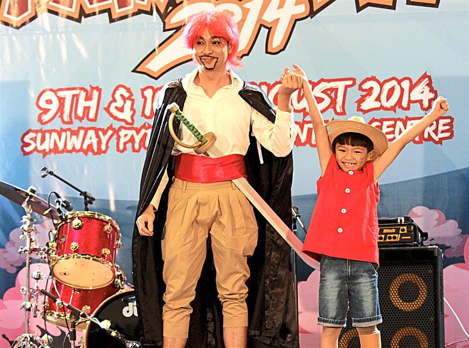 Onstage at Sunway Pyramid Convention Centre, costumed actors wave to the crowd after successfully getting them to make sympathetic and jubilant noises in a video short for AniManGaki 2014.