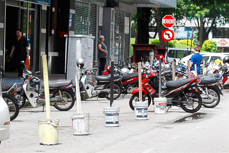 3 Obstacles have been placed on these parking lots to prevent the public from parking their cars in Bandar Baru Air Itam. Photos:CHAN BOON KAI and LIM BENG TATT