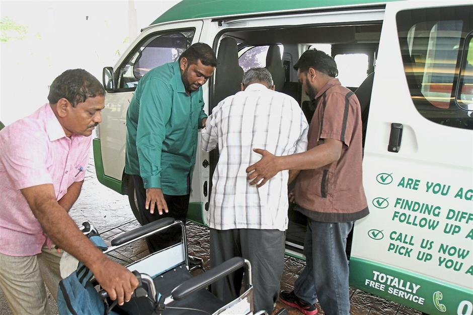 Social service: Sashitharaan (in green shirt) and Chandrasegaran (in brown shirt) assisting a patient into the van following a dialysis session at a private medical centre in Klang.