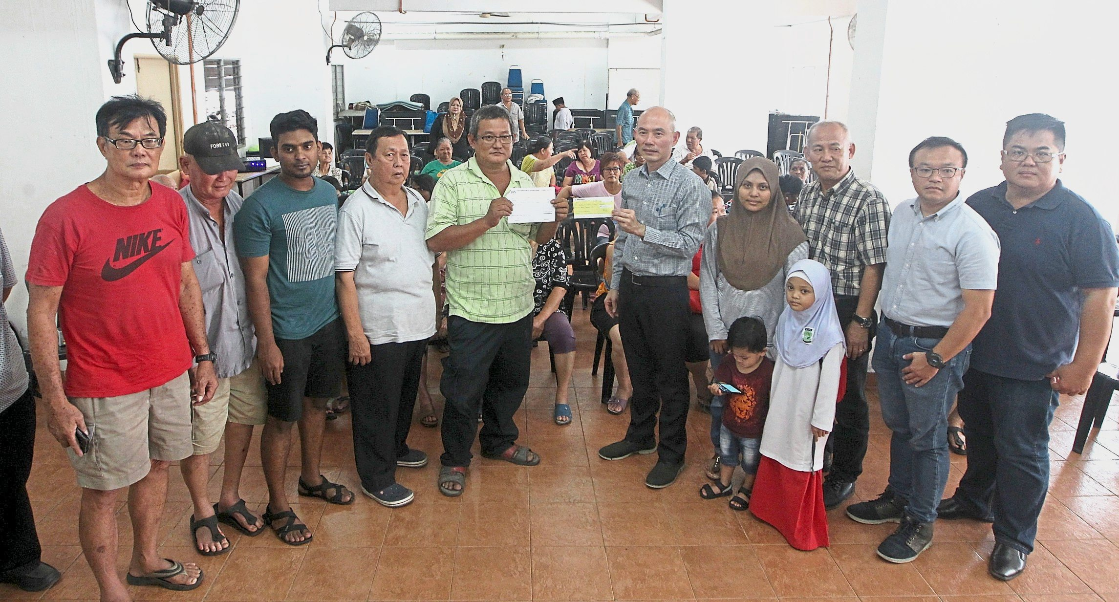 Lim (sixth from left) handing over the RM20,000 contribution to Song (fifth from left).