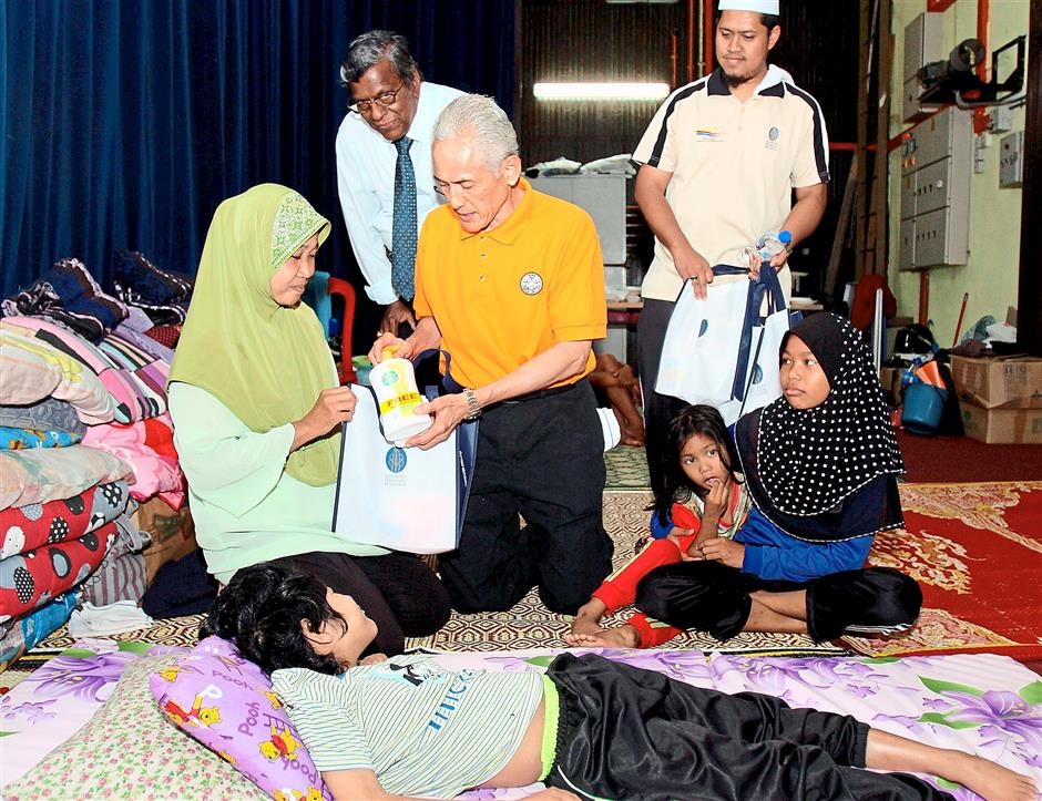 Aid: Dr Abdul Rahim (centre) giving out hygiene products to flood victim Rosmah Suhaimi, 45 (left) who is taking shelter with her children at SMK Muzaffar Shah flood relief centre.