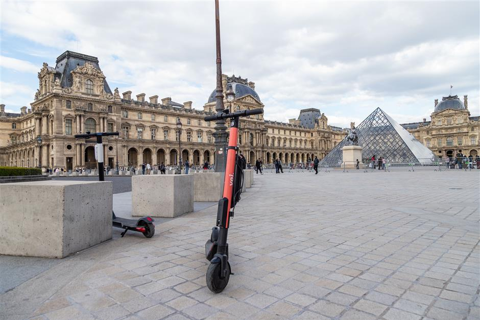 A Voi Technology AB public hire e-scooter stands outside the Louvre Museum in Paris, France, on Thursday, May 16, 2019. Uber Technologies Inc. is producing nearly 1,000 Jump-branded electric bikes a day and has a $1 billion budget for scooters, bikes and other mobility initiatives. Photographer: Anita Pouchard Serra/Bloomberg