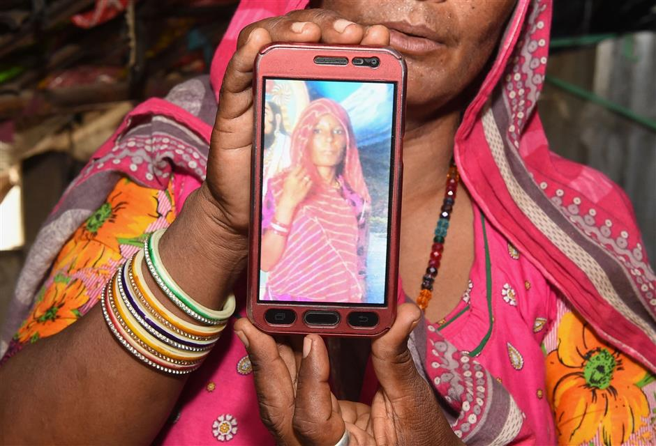 Mohinidevi Nath displays a photo on a mobile phone of her cousin Shantadevi Nath, who was killed by a mob that falsely believed she was intent on abducting children, on the outskirts of Ahmedabad in India\'s western Gujarat state on June 27, 2018. Indian police urged people on June 27 not to believe false rumours spread on WhatsApp after a woman was killed and a dozen hurt in the latest mob attacks to leave authorities looking powerless. / AFP PHOTO / SAM PANTHAKY