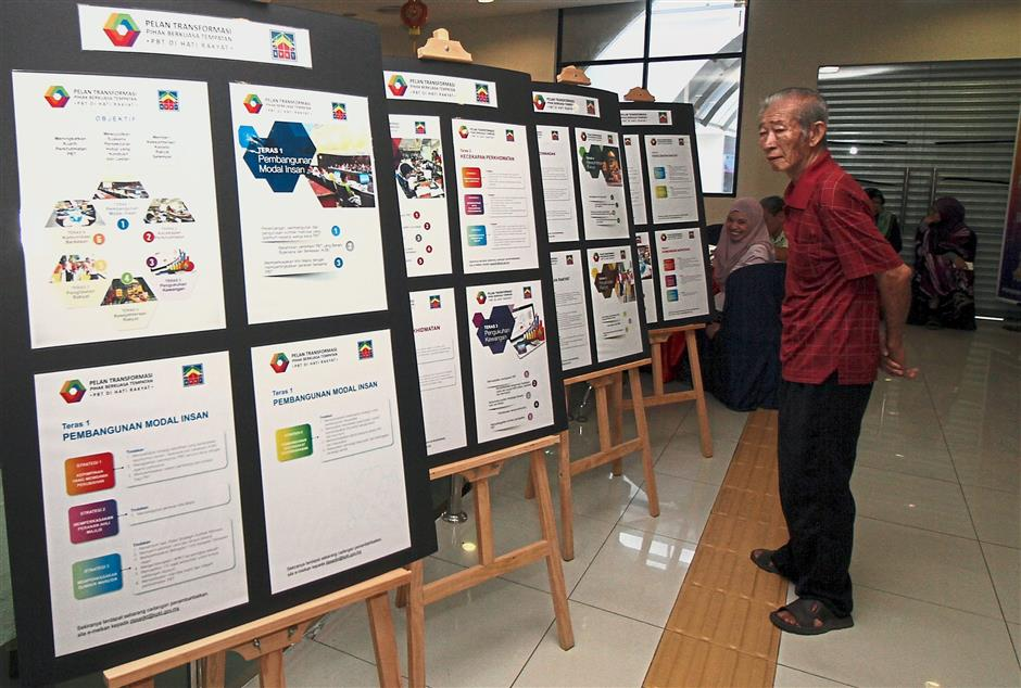 A senior citizen looking at a local council transformation plan on display at the Urban Transformation Centre. Ipoh residents hope more infrastructure can be built for the elderly.