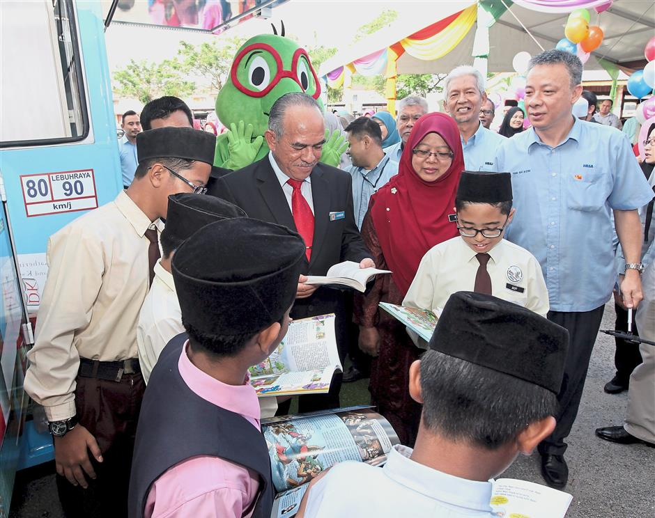 Ahmad Zaharin (centre, wearing red tie) checking out the books with pupils.