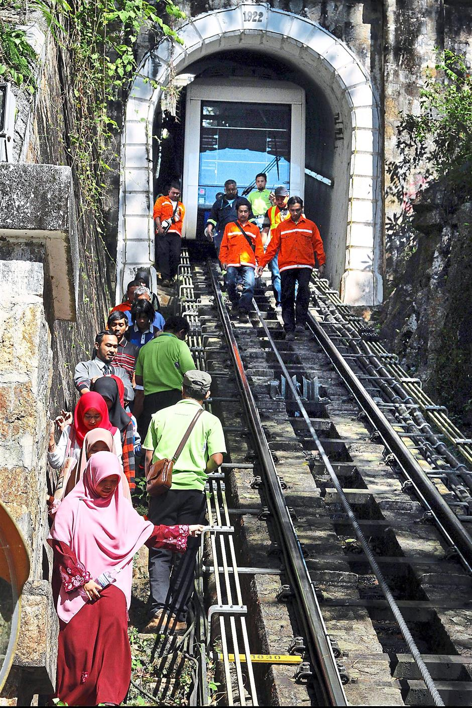Long way down: Passengers taking the narrow staircase by the side of the funicular railway tracks at Penang Hill.