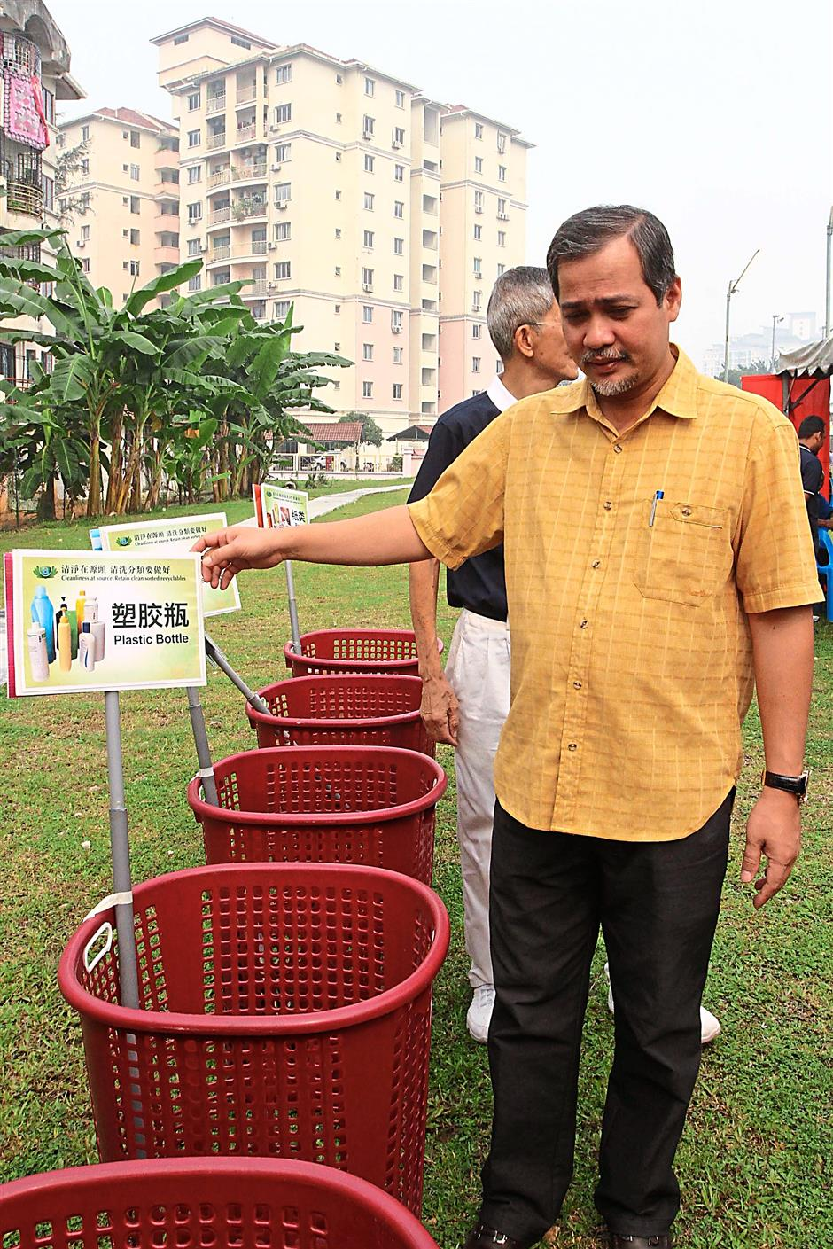 Abdul Hamid demonstrating how recyclable waste should be separated and thrown into the correct bins.