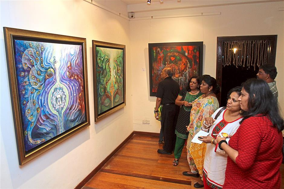 In awe: Visitors checking out the paintings of 'Wonder, Stillness, Life Answered' at the Sutra Gallery.