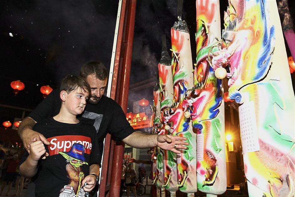 Australian Richard, from Perth, showing his son Tom the giant dragon joss sticks at the Hai Choo Soo Temple.