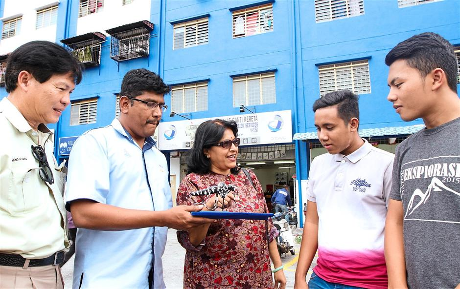 Dr. Chitra (second from left) explaining to teenagers Muhd Hazman Abu Kassim (third from left) and Shahfikri Ramli (fourth from left) outside the Impian Baiduri Apartments on how to note a Aedes mosquito while senior health inspectors Selva Rathnam look on with the replica of the mosquito.