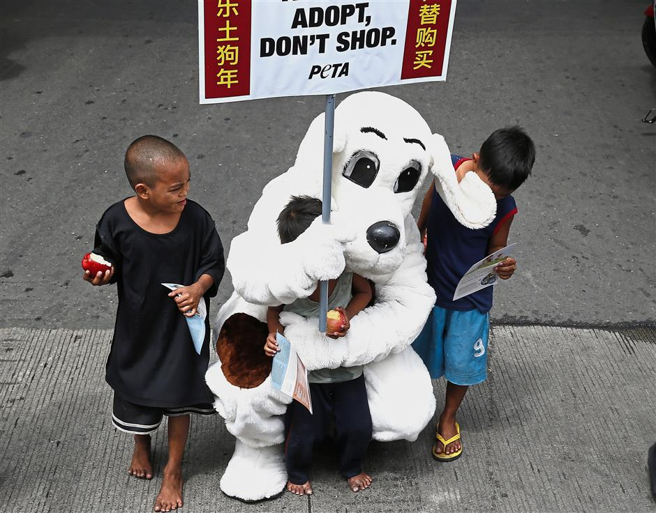 A dog mascot of the People for the Ethical Treatment of Animals, P.E.T.A., plays with street children as he distributes flyers to passengers at Manilas Chinatown district to call for people to adopt dogs instead of buying purebreds from breeders ahead of the Chinese New Year celebration for the Year of the Dog Monday, Feb. 12, 2018 in Manila, Philippines. (AP Photo/Bullit Marquez)