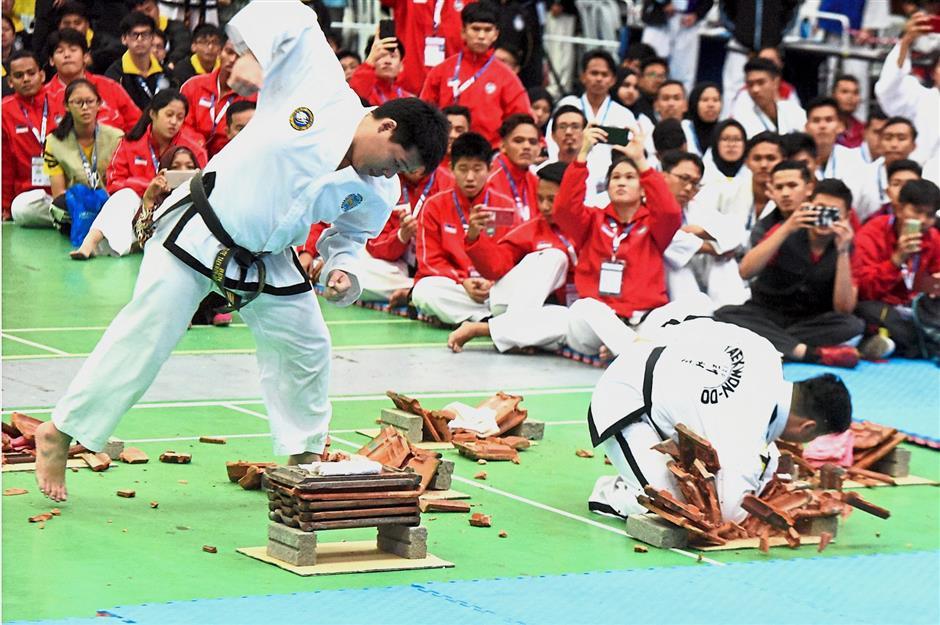 Two competitors using their elbows to break tiles.