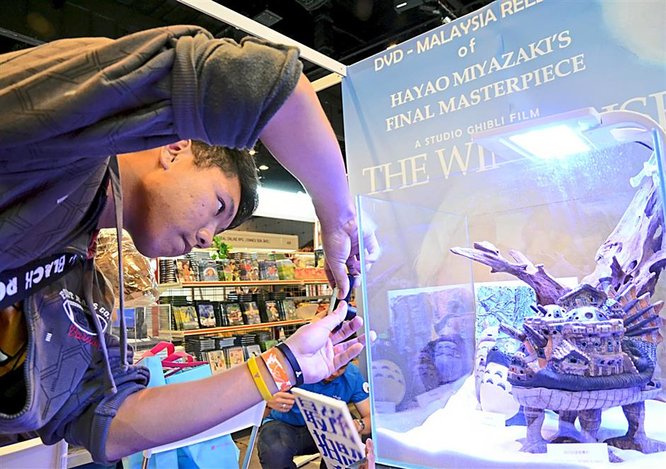 A visitor to AniManGaki 2014 takes a picture of various dioramas depicting Hayao Miyazaki's works during the 2-day gathering. The diorama in the foreground is from Howl's Moving castle.
