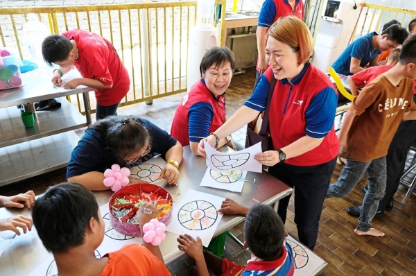 Da Ma Cai volunteers and differently-abled children having fun during craft time at the Handicapped and Disabled Childrenu2019s Association of Klang, Selangor.