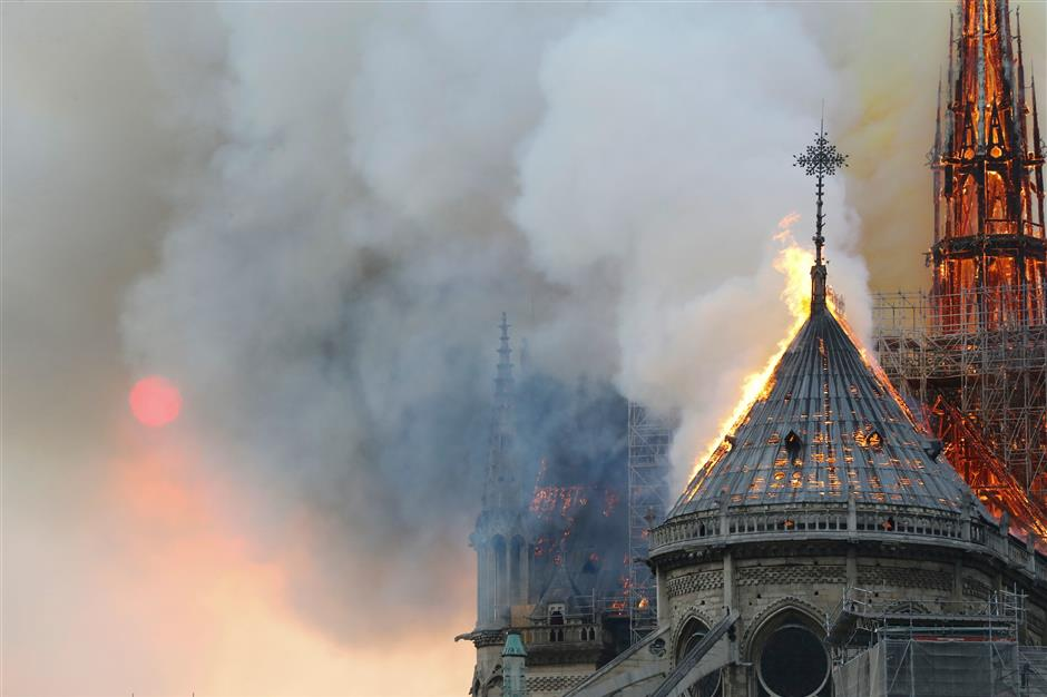 Flames burn the roof of the landmark Notre-Dame Cathedral in central Paris on April 15, 2019, during a fire. - A major fire broke out at the landmark Notre-Dame Cathedral in central Paris sending flames and huge clouds of grey smoke billowing into the sky, the fire service said. The flames and smoke plumed from the spire and roof of the gothic cathedral, visited by millions of people a year, where renovations are currently underway. (Photo by FRANCOIS GUILLOT / AFP)