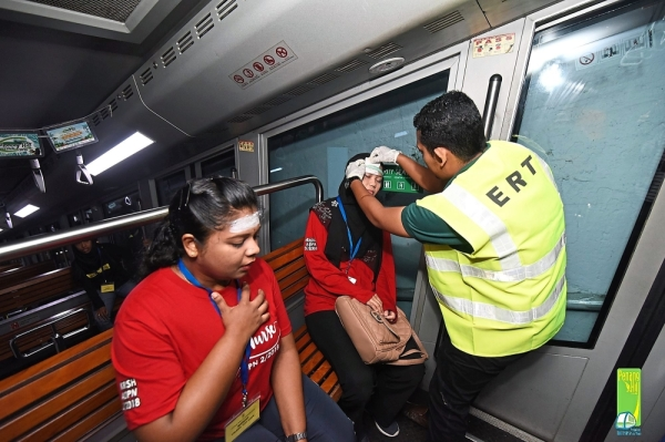An 'injured train passenger' receiving treatment from a member of the rescue team. (Right pic) 'Passengers' being guided to safety.
