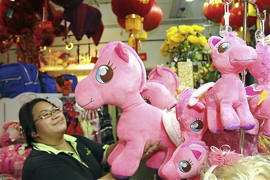 Julie looking at the horse soft toys, thinking of getting some for upcoming chinese, is because this  year is the year of the horse in  chinese zodiac at Petaling Street in Kuala Lumpur on Thursday 02 January 2014. Brian Moh/The Star.