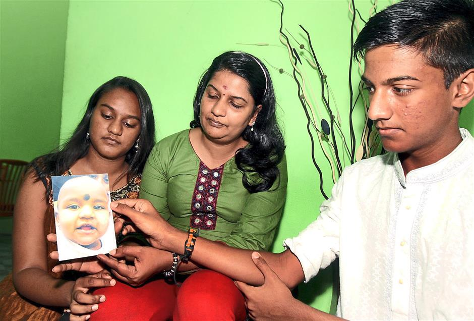 M. Indira Gandhi (middle), flanked by her daughter Tevi Darsiny (left) and son Karan Dinish (right), looking at a photo of her youngest daughter Prasana Diksa.