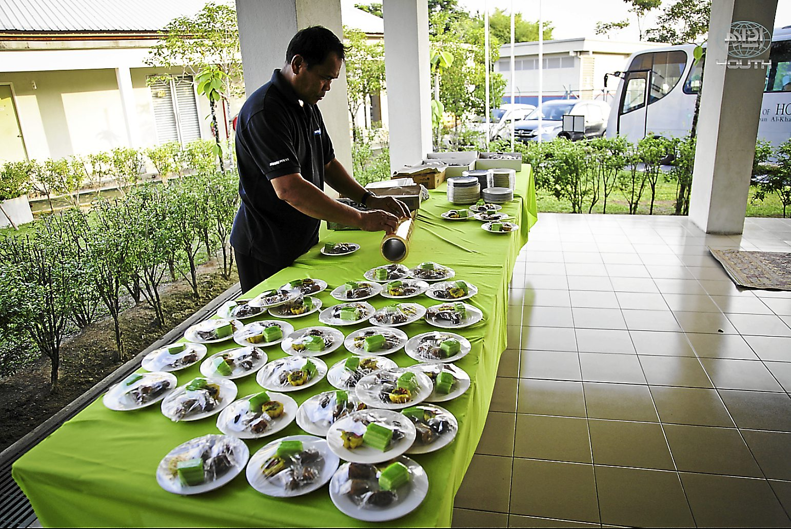A volunteer lays out plates of cakes at the Al-Khaadem children's home. The running home the home costs the foundation some RM