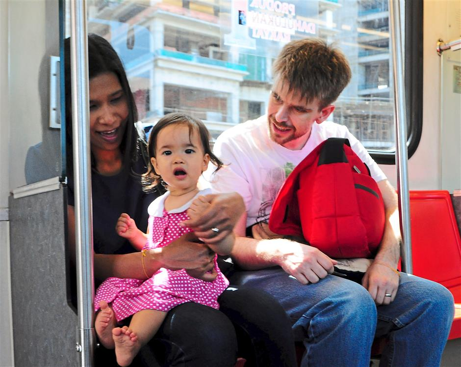 Emma gets the full attention of her parents Hse (left) and Bowman while travelling on the LRT.
